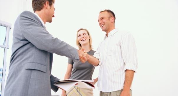 Man shaking hands with couple