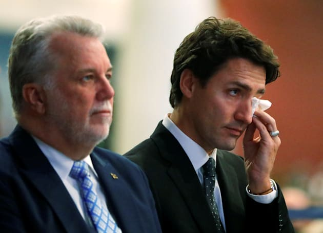 Prime Minister Justin Trudeau wipes a tear as he stands with Quebec Premier Philippe Couillard during...