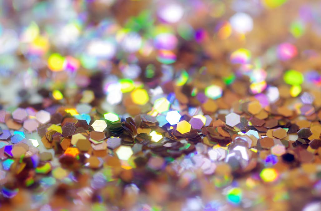 Close-up of silver glitter reflecting colors of the rainbow. Selective focus for bokeh effect.