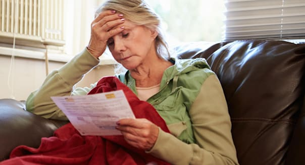 Worried Senior Woman Sitting On Sofa Looking At Bills