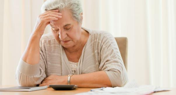 C25REN Retired woman calculating her domestic bills