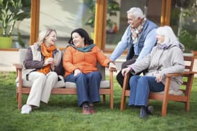Senior friends sitting together in front of their retirement community house.