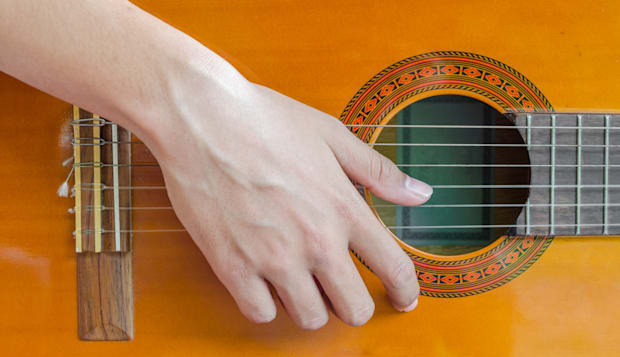 close up on a man playing guitar