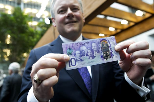 Stephen Poloz, governor of the Bank of Canada, stands for a photograph with a copy of a commemorative...