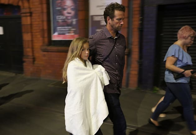 A young girl and a man leave the Manchester Arena, where 19 people died in an