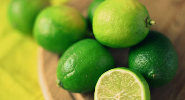 Green limes on yellow tablecloth and round wooden kitchen cutting board.