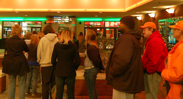 A crowd of people waiting in line for a ticket to a movie on a Friday night after work.