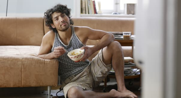 Young man sitting on floor, eating breakfast