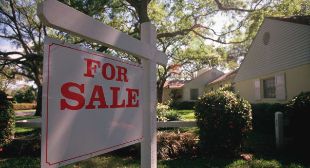 For sale sign hanging in front of house