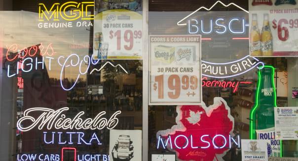Beer signs in neon in liquor store window