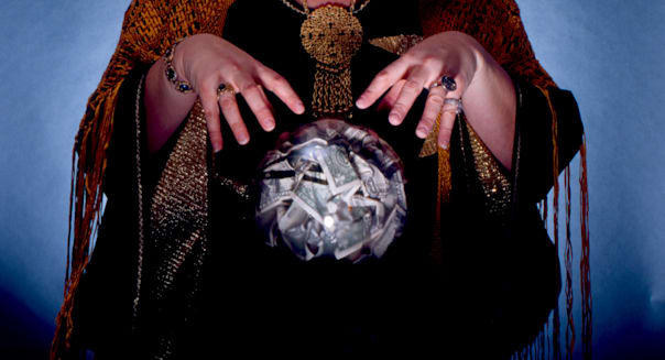 Fortune Teller Looking Into Crystal Ball, Filled With Money. (Photo by Education Images/UIG via Getty Images)
