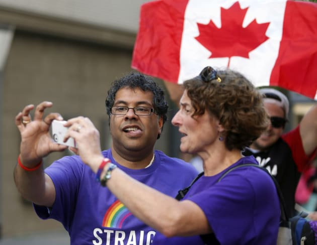 Calgary Mayor Naheed Nenshi and another marcher take a photo while marching in a gay pride parade in...