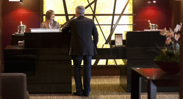 Businessmen speaking with staff at the front desk reception of a luxury hotel.