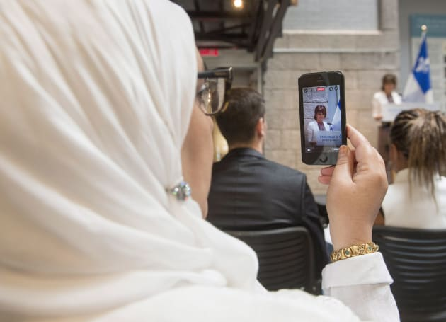 A woman records on her phone as Quebec Immigration, Diversity and Inclusiveness Minister Kathleen Weil...