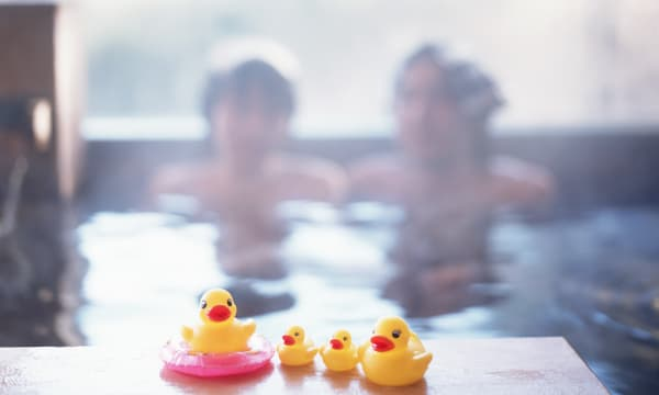 Couple relaxing in hot tub, rubber ducks in foreground