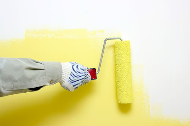 hand painting a white wall with ...