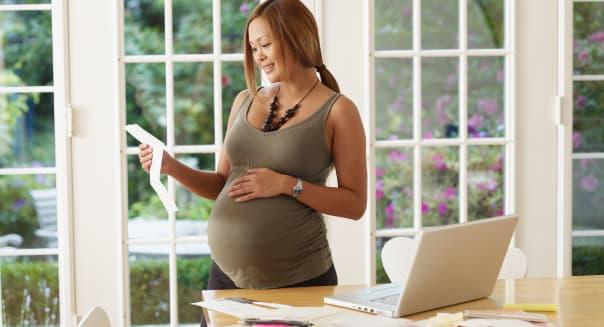 Pregnant Asian woman looking at bills