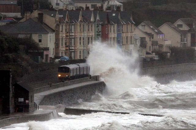 A train is battered by waves as it passes through the Dawlish train station, Devon
