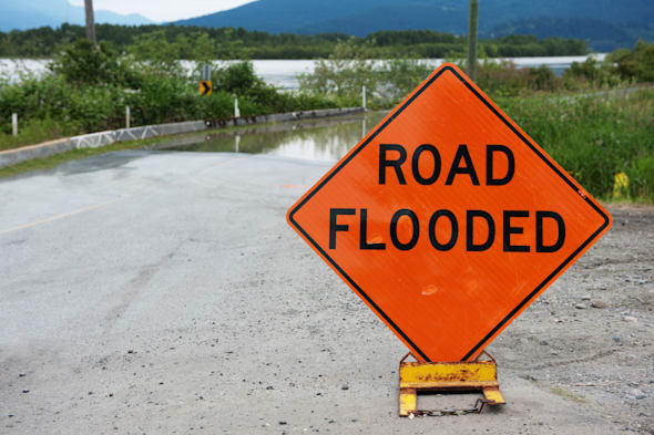 Orange caution sign saying road flooded against Fraser river flooding over road.