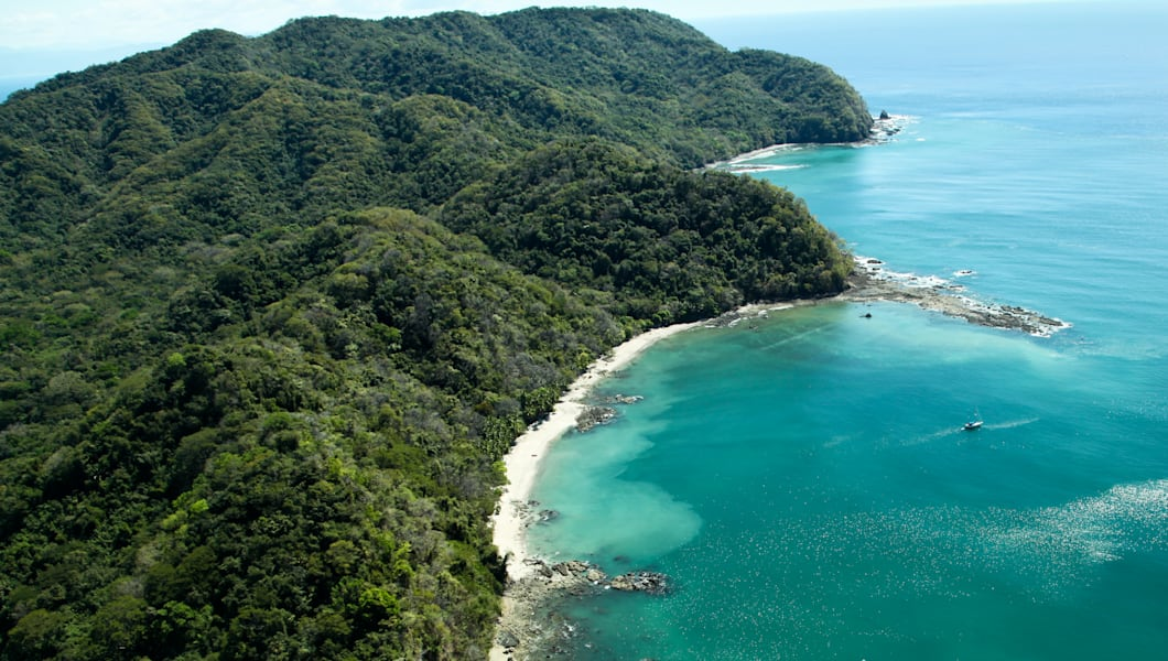 Lush jungle covered mountains stretch out into the Gulf of Nicoya next to the rocky and sandy beach of Ballena Bay in Costa Rica