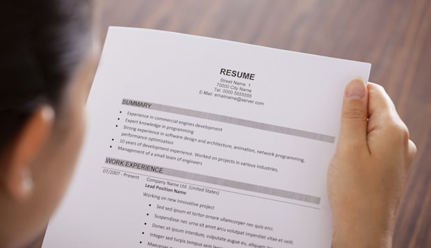 Close-up Of Young Businesswoman Reading Resume At Desk