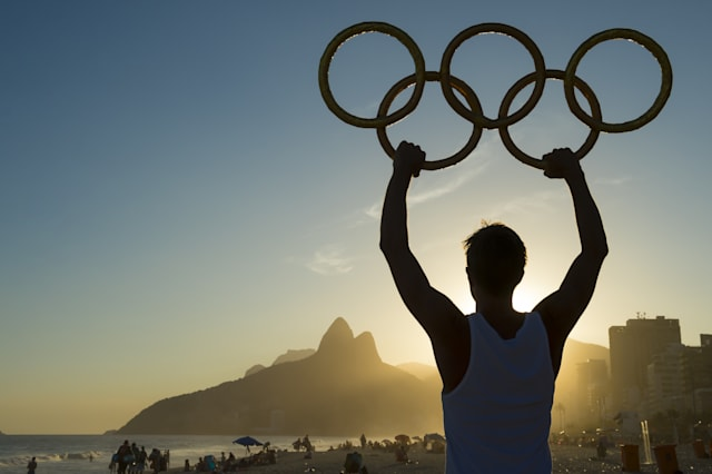 RIO DE JANEIRO, BRAZIL - MARCH 05, 2015: Athlete holding Olympic rings above sunset city skyline view of Two Brothers Mountain a