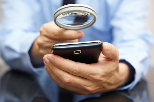 Businessman using mobile smart phone with magnifying glass