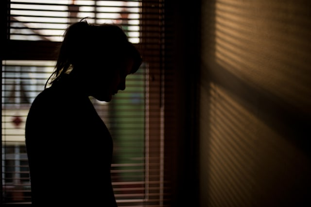 Silhouette of woman by window