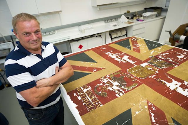Gary Lawrence age 58 with his Waterloo flag. See National copy NNFLAG: A military antiques collector has discovered one of the last remaining flags from the Battle of Waterloo in a shoe box. Gary Lawrence bought the collection of items through an online auction and found fragments of the flag, which dates back 200 years. He is now restoring the flag, which belonged to the Coldstream Guards 15th Light Company, with a team from the V&A museum. The 58-year-old runs Waterloo Militaria with his son Luke, and says he has never found anything this historically significant.