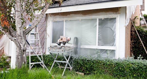 A tile saw and ladder in front of a plastic covered window during a home remodel.