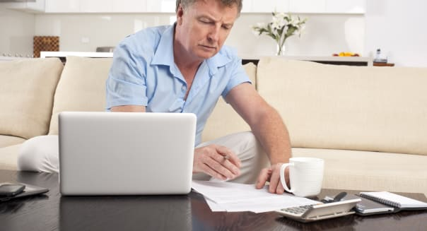 mature man doing paperwork with laptop retirement taxes