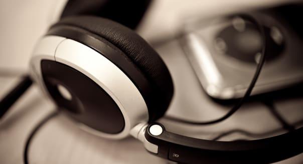 Headphones next to a black iPod on a desk -Title:   Headphones and iPodCaption:  Headphones next to a black iPod on a deskC
