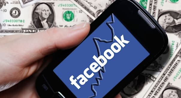 Hand holding a smartphone with a Facebook logo in front of dollar bills, symbolic image for the Facebook IPO