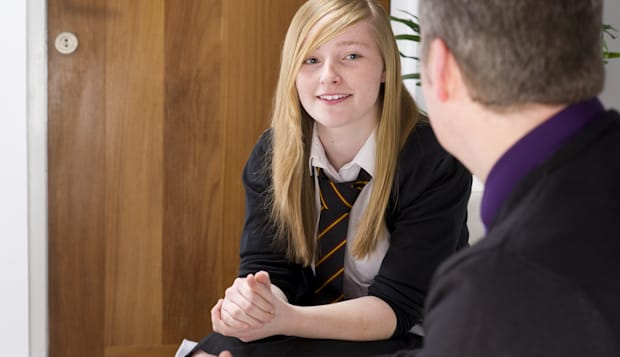 high school student chats to teacher or counsellor