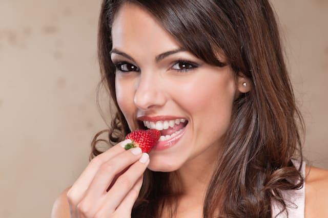 Portrait of pretty young woman eating a strawberry