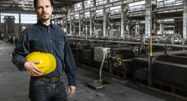 Mid Adult worker with yellow helmet against factory interior