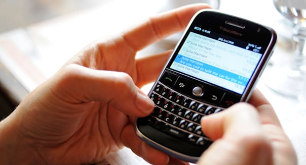 A woman using a Blackberry phone to send and receive emails and text messages over the Internet.