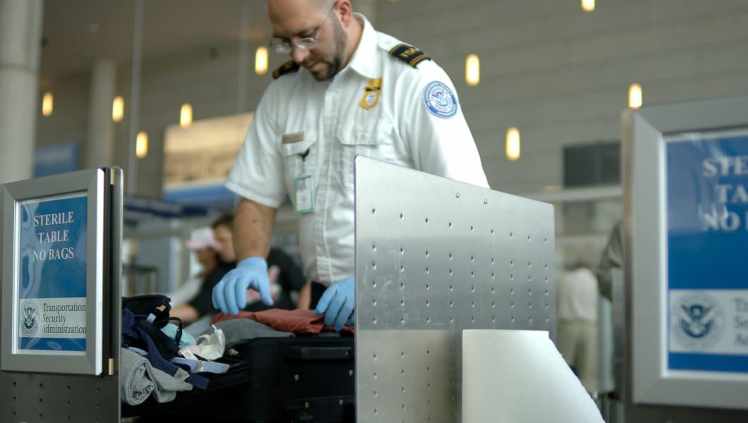 a tsa agent searches luggage at ...