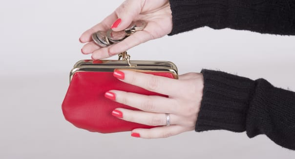 Woman holding money and a red purse