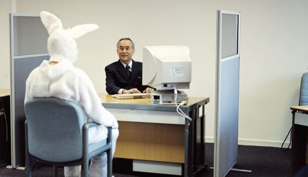 Man wearing rabbit suit at desk opposite mature businessman