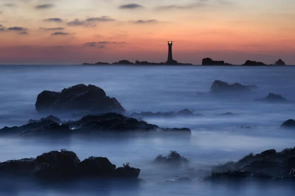Last light over Hanoix Lighthouse creating a misty, eery view of the coastline near Hanoix in Guernsey.