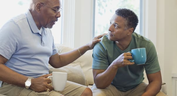 Senior father and son talking while having coffee on sofa