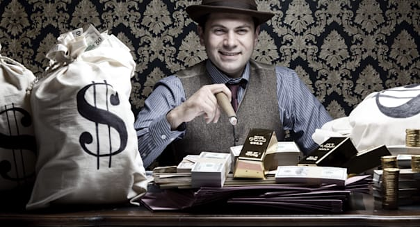 Rich man posing with money bags and dollar bills