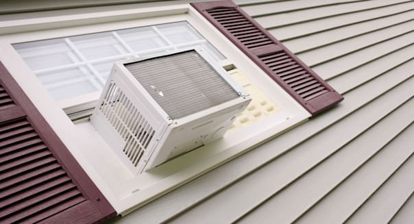 Air conditioner in house window with gray siding