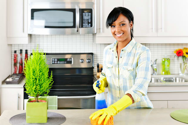 C17B2T Smiling young black woman with sponge and rubber gloves cleaning kitchen spring cleaning woman; cleaning; smiling; kitche