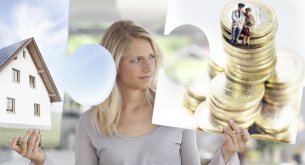 Mid adult woman holding large jigsaw pieces of a house and money