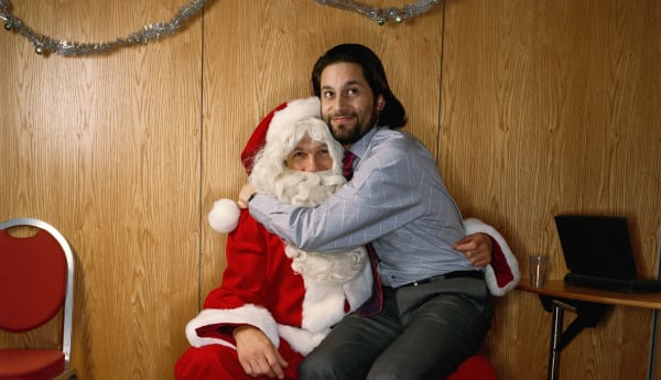 Man sitting on knee of man dressed as Santa