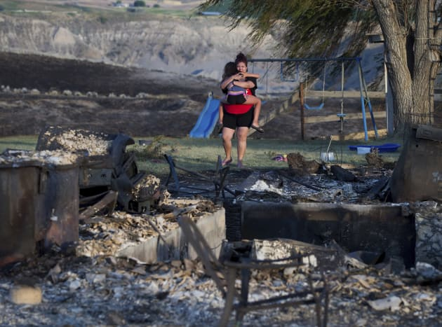 Kelsey Thorne holds her daughter Nevaeh Porter, 8, as they both cry while viewing the remains of their...