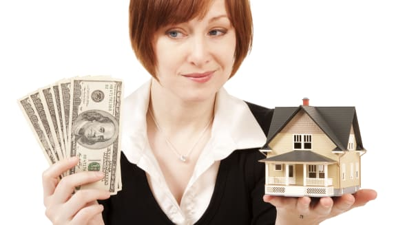 Worried woman cash in hand and model house