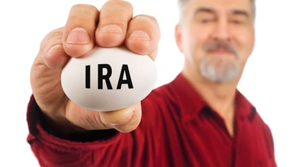 Mature man holds a nest egg with IRA on it. IRA: Individual Retirement Account, a popular investment tool in the United States